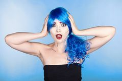 Portrait of young woman in comic pop art make-up style. Shoked. Female in blue wig on blue background Stock Images