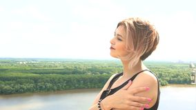 Portrait of young woman in countryside summer during windy day with river, trees, forest in background.  stock footage