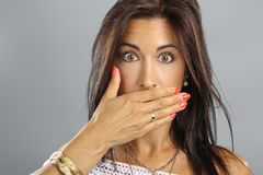 Portrait of young woman covering her mouth. With hand against a grey background Stock Image