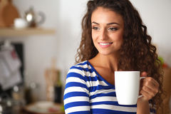 Portrait of young woman with cup against kitchen Stock Photo