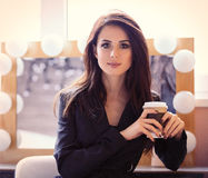 Portrait of young woman with cup of coffee. Portrait of young beautiful woman with cup of coffee sitting on the chair Royalty Free Stock Images