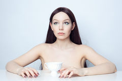 Portrait of a young woman with a cup of tea. Studio photo brunette at the table Stock Photos