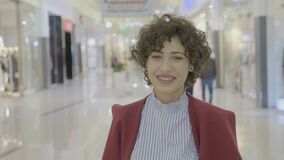 Portrait of a young woman with curled hair smiling winking and posing in a fashion way in the mall during her shopping break -. Portrait of a young woman with stock video
