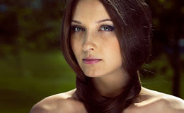 Portrait of young woman with dark brown hair. Attractive girl with long straight dark brown hair against nature background royalty free stock images