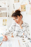 Portrait of a young woman designer drawing sketches. At ter workplace in studio Stock Images