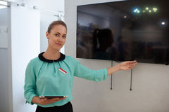 Portrait of a young woman designer points to the tv screen with copy space for your text message or promotional content stock images