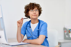 Thinking Female Doctor at Desk in office royalty free stock photos
