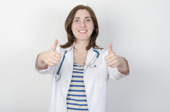 Portrait of young woman doctor with two thumbs up. Female doctor young with stethoscope two thumbs up Stock Photography