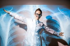 Doctor on the x-ray of human lungs background. Portrait of a young woman doctor in uniform with projected x-ray of human lungs Royalty Free Stock Image