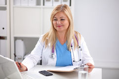 Portrait of young woman doctor in white coat at Stock Photo