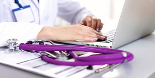 Portrait of young woman doctor in white coat at computer Stock Photography