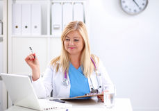 Portrait of young woman doctor in white coat at Royalty Free Stock Photos
