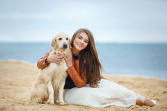 Portrait of a young woman with a dog on the beach Royalty Free Stock Image