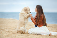 Portrait of a young woman with a dog on the beach Stock Images