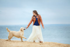 Portrait of a young woman with a dog on the beach Royalty Free Stock Images