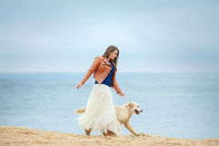 Portrait of a young woman with a dog on the beach Stock Photo