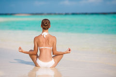 Portrait of young woman doing yoga exercises on tropical maldivian beach near ocean Royalty Free Stock Photos