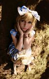 Portrait of young woman dressed as doll, near tree Stock Photo