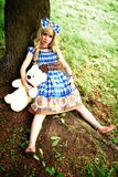 Portrait of young woman dressed as doll, near tree Royalty Free Stock Photo