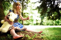Portrait of young woman dressed as doll, near tree Stock Image