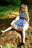 Portrait of young woman dressed as doll, near tree Stock Images