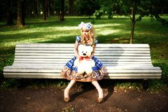 Portrait of young woman dressed as doll sitting on bench Stock Image