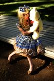 Portrait of young woman dressed as doll sitting on bench Royalty Free Stock Photos