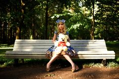 Portrait of young woman dressed as doll sitting on bench Stock Photography