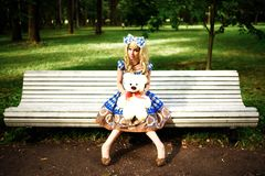 Portrait of young woman dressed as doll sitting on bench Stock Photo