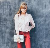 Portrait of a young woman dressed in a blouse, red Chino Trouser, a handbag turquoise on her shoulder. Posing next to a gray wall. Stock Image