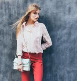 Portrait of a young woman dressed in a blouse, red Chino Trouser, a handbag turquoise on her shoulder. Posing next to a gray wall. Stock Images