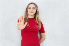 Portrait of young woman dressed in red dress making stop gesture with her hand. Cropped isolated portrait of blonde female standin royalty free stock photography
