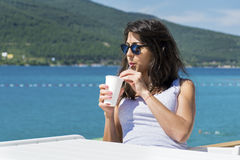 Portrait of  young woman  drinking coffee  on the beach Royalty Free Stock Photo