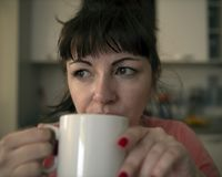 Young woman drinks coffee in the morning in the kitchen, tired eyes with red veins, close-up stock photo