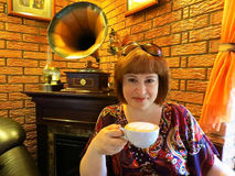 Portrait of a young woman drinking coffee. Sitting next to the fireplace and the phonograph Royalty Free Stock Image