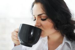 Portrait of young woman drinking a cup of coffee. Portrait of young woman drinking a cup of coffee Royalty Free Stock Image