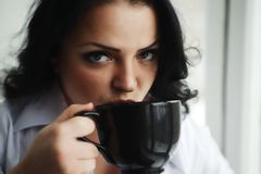 Portrait of young woman drinking a cup of coffee. Royalty Free Stock Image