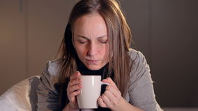 The portrait of the young woman drinking the hot tea. Close-up. 4K. stock footage
