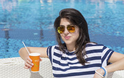 Portrait of  young woman  drinking juice on the pool Stock Photo