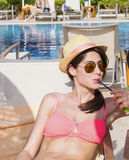 Portrait of  young woman  drinking juice on the pool Stock Photos