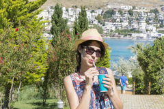 Portrait of  young woman  drinking juice on a sea background Stock Images
