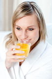 Portrait of a young woman drinking an orange juice Stock Image