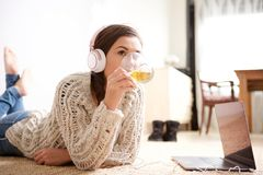 Young woman drinking tea and listening to music with headphones. Portrait of young woman drinking tea and listening to music with headphones Royalty Free Stock Photos