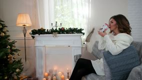 Portrait of a young woman drinking tea, in the living room near Christmas tree, happy girl drinks tea, smiling looks stock video