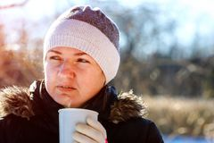 Portrait of young woman drinking tea outdoors at winter street. Stock Photo
