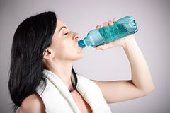 Portrait of young woman drinking water. With eyes closed.Brown background Stock Photo