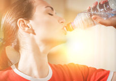 Portrait of young woman drinking water from bottle against the s royalty free stock images