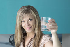 Portrait of a young woman drinking water in the kitchen at home Stock Image