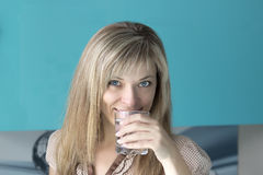 Portrait of a young woman drinking water in the kitchen at home Royalty Free Stock Images