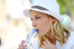 Portrait of young woman drinking water in summertime Stock Photography
